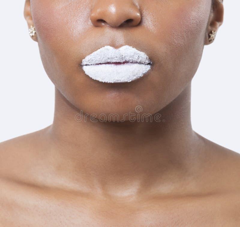 El primer tiró de mujer afroamericana joven con los labios blancos sobre el fondo blanco imagenes de archivo