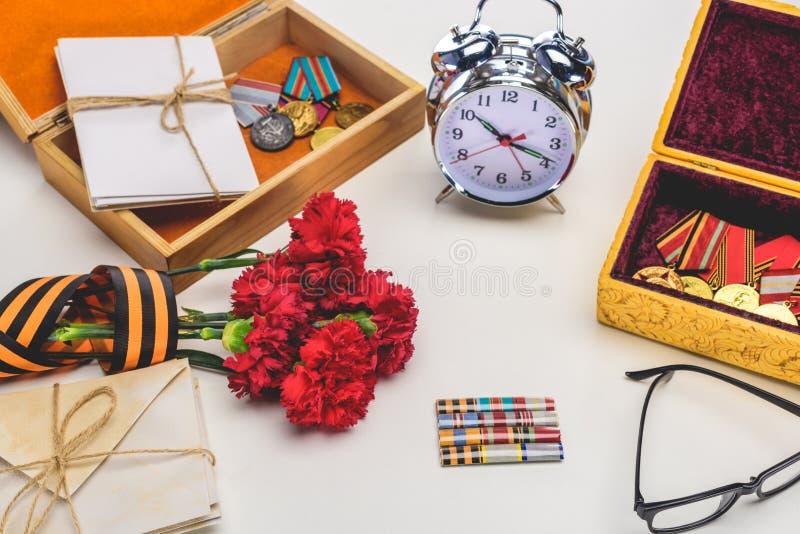 el primer tiró del despertador, lentes, flores envueltas por la cinta de San Jorge, letras, medallas en el gris, concepto del día foto de archivo libre de regalías