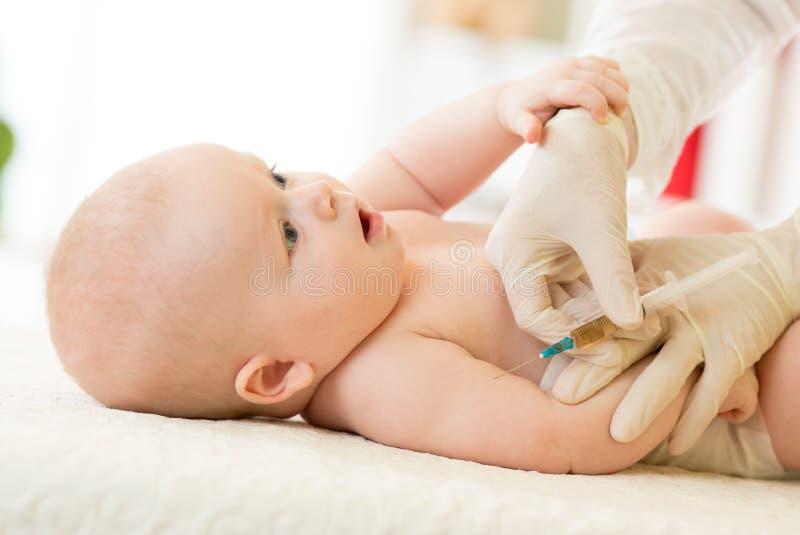 El primer tiró del pediatra que daba a bebé la inyección intramuscular en brazo fotografía de archivo