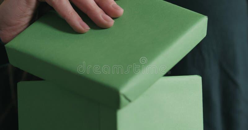 El primer tirado de manos femeninas jovenes abre la caja de regalo del Libro Verde foto de archivo libre de regalías