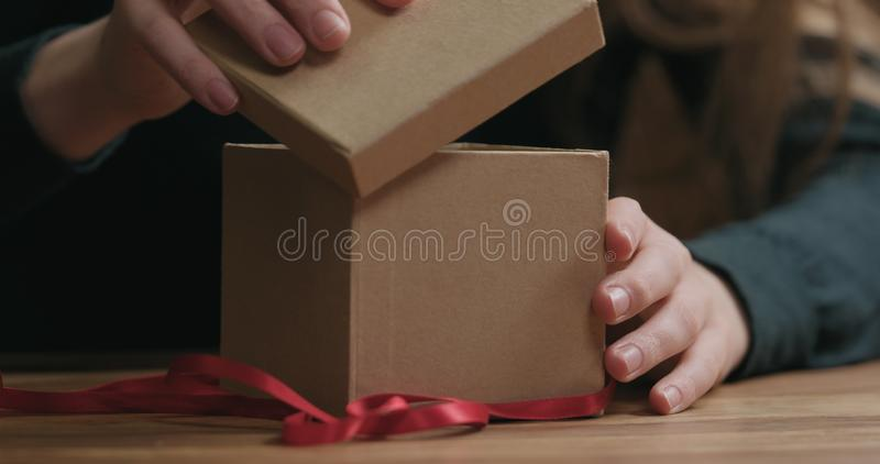 El primer tirado de manos femeninas jovenes abre la caja de regalo del papel del arte con el arco rojo de la cinta imágenes de archivo libres de regalías