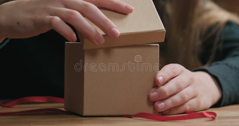 El primer tirado de manos femeninas jovenes abre la caja de regalo del papel del arte con el arco rojo de la cinta fotos de archivo libres de regalías