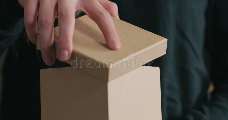 El primer tirado de manos femeninas jovenes abre la caja de regalo del papel del arte con el arco rojo de la cinta fotografía de archivo