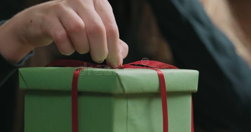 El primer tirado de manos femeninas jovenes desata el arco rojo de la cinta en la caja de regalo del Libro Verde imagenes de archivo