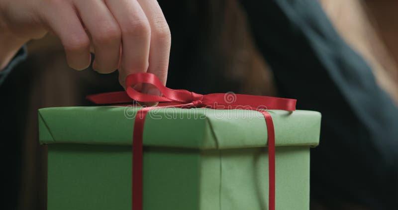 El primer tirado de manos femeninas jovenes desata el arco rojo de la cinta en la caja de regalo del Libro Verde fotos de archivo libres de regalías