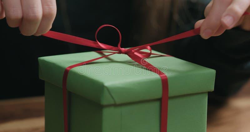 El primer tirado de manos femeninas jovenes desata el arco rojo de la cinta en la caja de regalo del Libro Verde foto de archivo