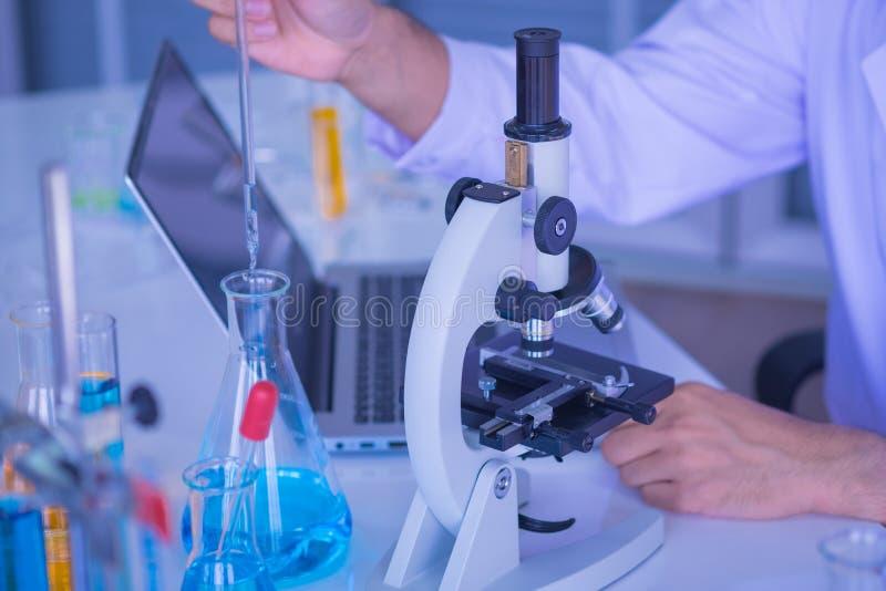 El primer tirado de microscopios y los científicos del hombre de la mano están probando la investigación con los tubos imágenes de archivo libres de regalías