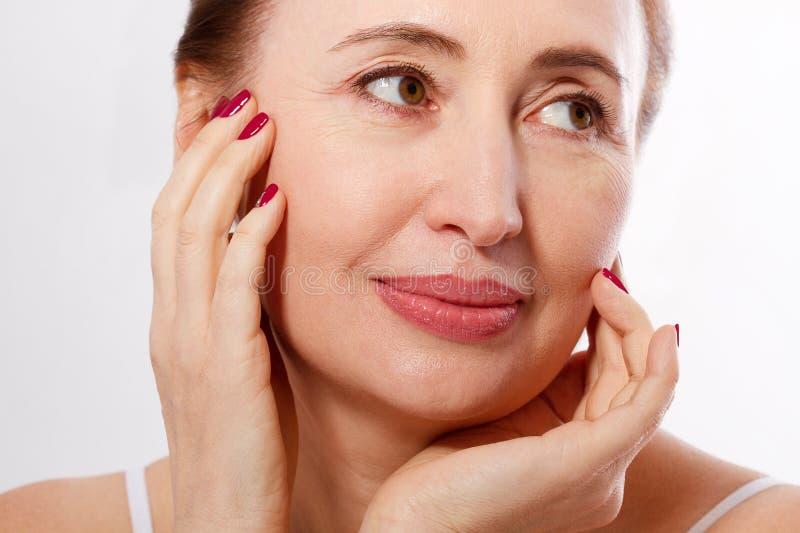 El primer y el retrato de la macro del centro hermoso y sano envejecieron la cara de la mujer en el fondo blanco Arrugas y menopa foto de archivo