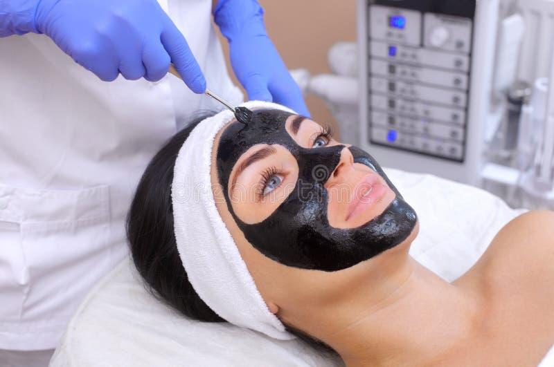El procedimiento para aplicar una máscara negra a la cara de una mujer hermosa imagen de archivo libre de regalías