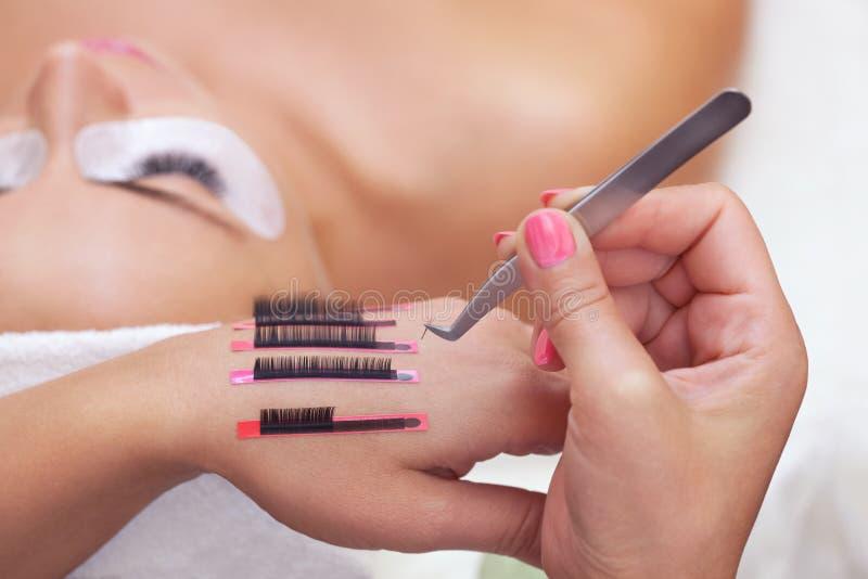 El procedimiento para las extensiones en el salón de belleza, pestañas de la pestaña en la mano del artista de maquillaje imágenes de archivo libres de regalías