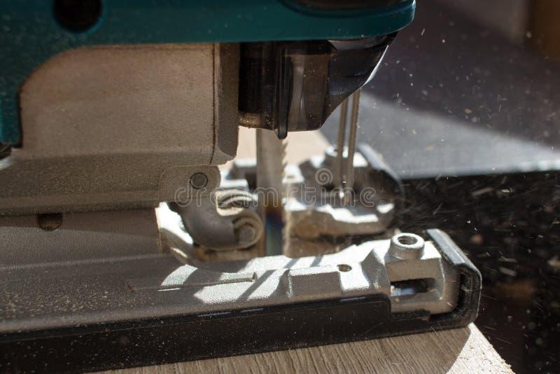 El proceso de aserrar a un tablero de madera con un rompecabezas de la manitas foto de archivo