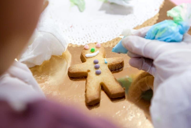 El proceso de hacer coco las galletas aplica manualmente el esmalte de su children& x27; manos de s foto de archivo