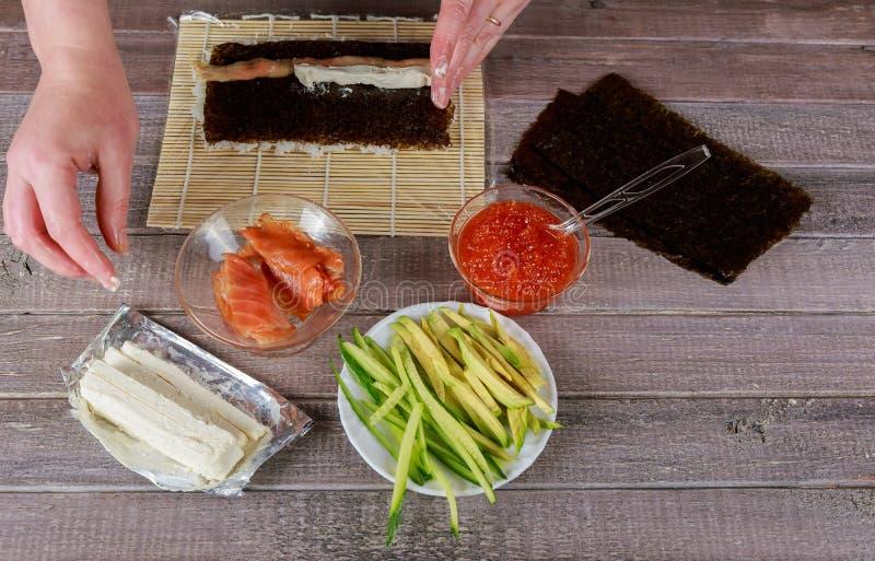 El proceso de hacer el sushi y los rollos fotos de archivo libres de regalías