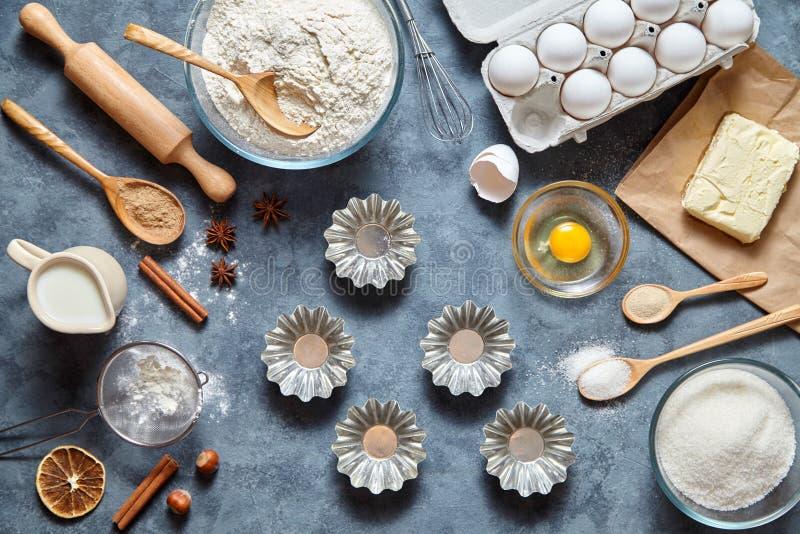 El proceso de hacer la pasta de la torta Ingredientes de la hornada para los pasteles hechos en casa en fondo oscuro Visión super imagenes de archivo