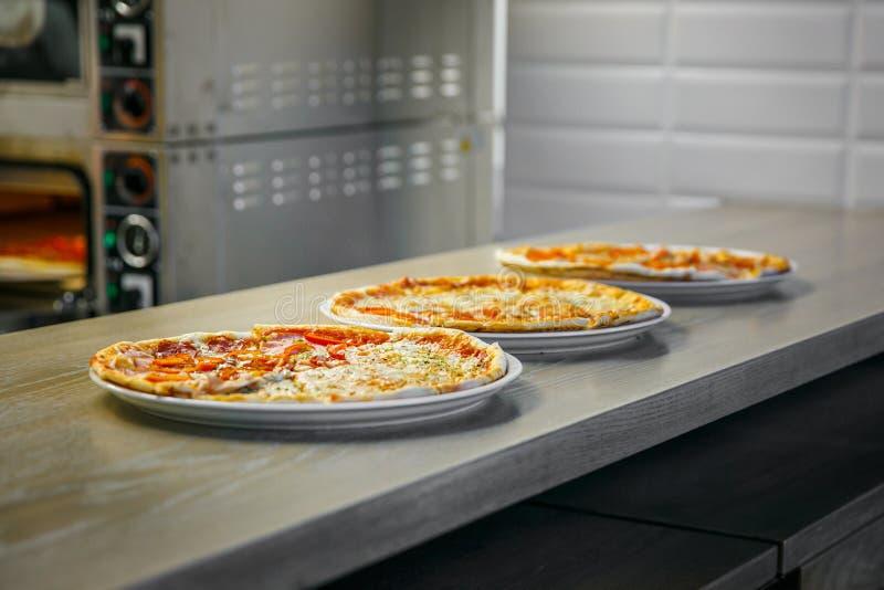 El proceso de hacer tres pizzas fotografía de archivo libre de regalías