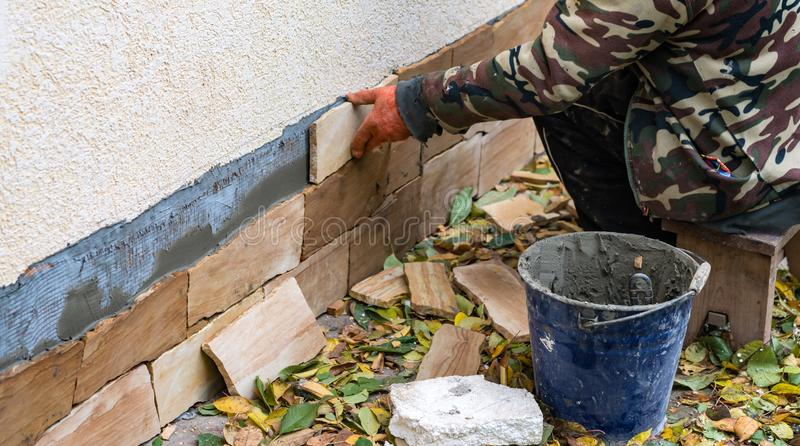 El proceso de instalar las tejas decorativas de la piedra arenisca fotografía de archivo