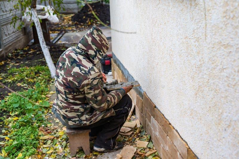 El proceso de instalar las tejas decorativas de la piedra arenisca fotos de archivo