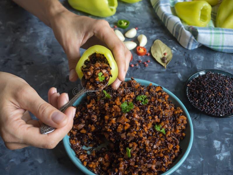 El proceso de la colocación que rellena dentro de la pimienta Pimientas rellenas con arroz y verduras negros Alimento biológico v fotografía de archivo