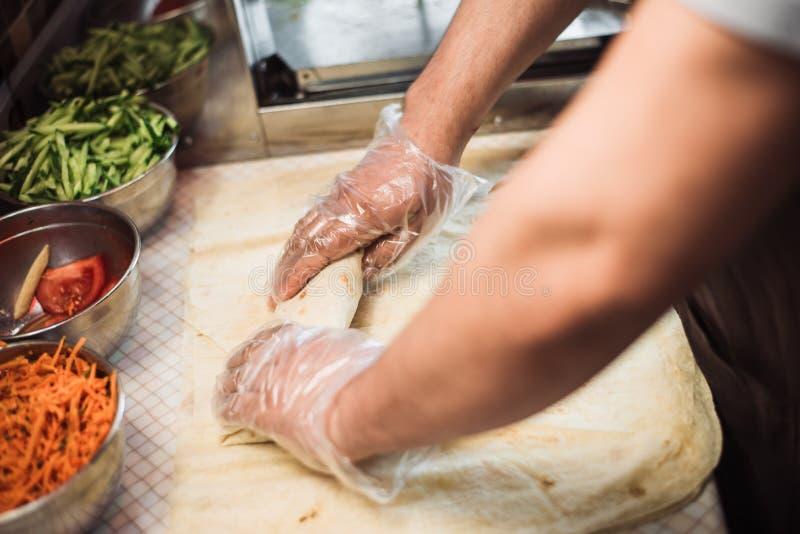El proceso de la torsión y de la carne y del ciabatta del embalaje en pan Pita el cocinero envuelve shawarma imágenes de archivo libres de regalías