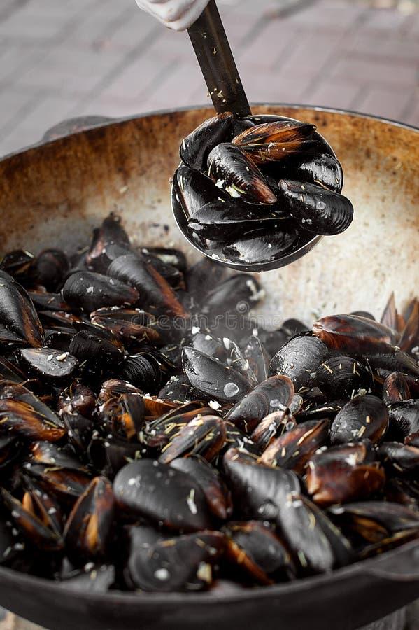 El proceso de preparar los mejillones en un cazo grande Comida de la calle con los mariscos imágenes de archivo libres de regalías