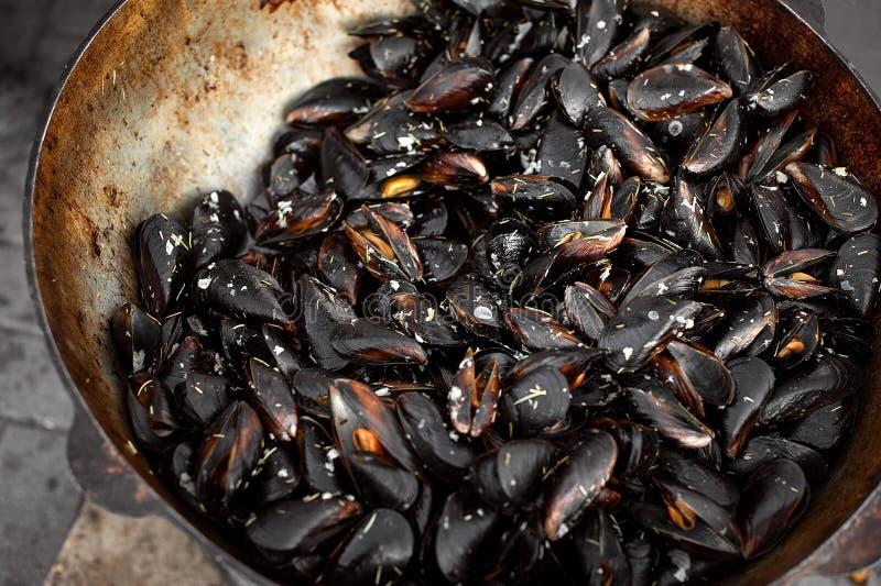 El proceso de preparar los mejillones en un cazo grande Comida de la calle con los mariscos foto de archivo