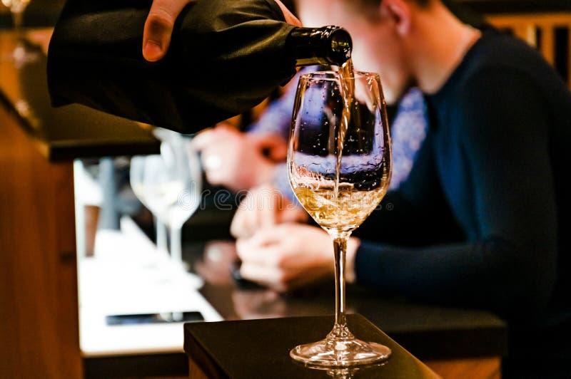 El proceso de verter el vino de una botella en un vidrio en el primero plano Entrenamiento en sommelier de la escuela Inconsútil  foto de archivo
