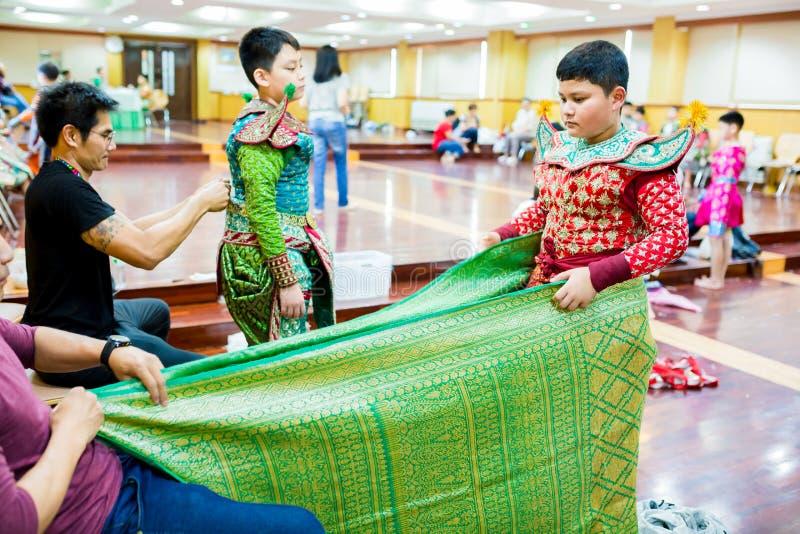 El proceso de vestir la pantomima tailandesa para los actores con la mano que cosen, reparando imagen de archivo
