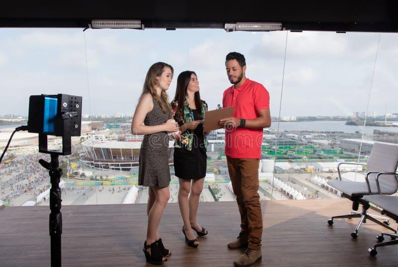 El productor de televisión da instrucciones a los presentadores femeninos en el estudio de la TV fotografía de archivo libre de regalías