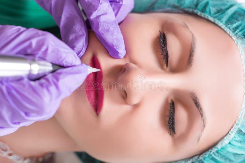 El profesional aplica procedimiento del maquillaje permanente en los labios de la mujer fotografía de archivo libre de regalías