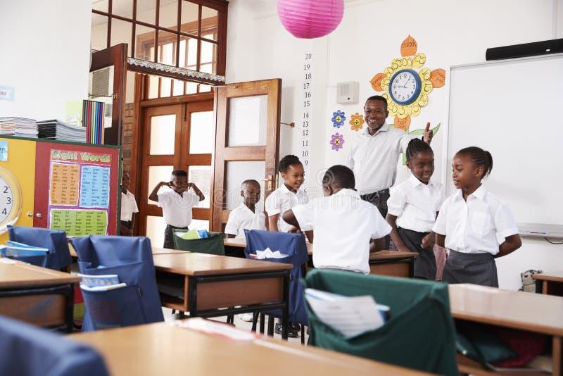 El profesor acoge con satisfacción a los niños que llegan a la clase de la escuela primaria fotografía de archivo libre de regalías