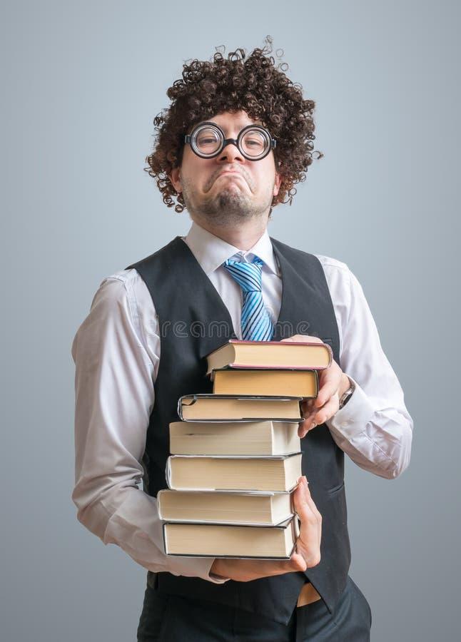 El profesor anormal divertido del empollón sostiene muchos libros en manos fotografía de archivo