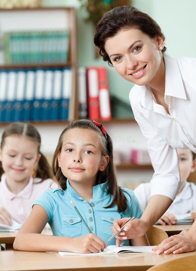 El profesor ayuda a pupilas a realizar la tarea fotos de archivo