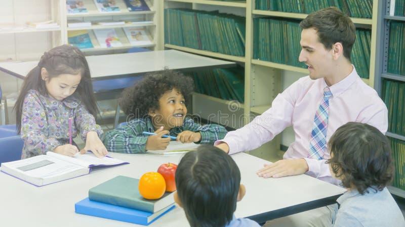 El profesor caucásico sonriente y el agrupar del asiático embroma al estudiante lear imagenes de archivo