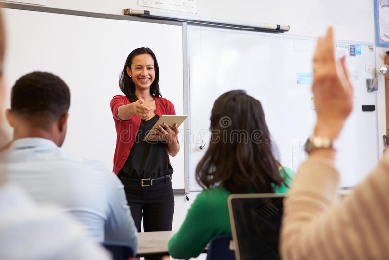 El profesor con la tableta y los estudiantes en una enseñanza para adultos clasifican fotos de archivo libres de regalías
