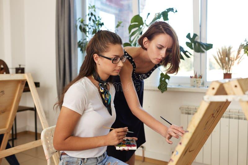 El profesor de dibujo ayuda a la muchacha morena joven en los vidrios vestidos en la camiseta blanca y vaqueros con una bufanda a fotos de archivo libres de regalías