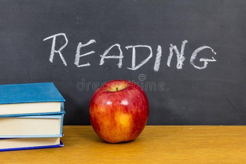 El profesor de la manzana de la sala de clase del libro de lectura leyó palabras imagen de archivo