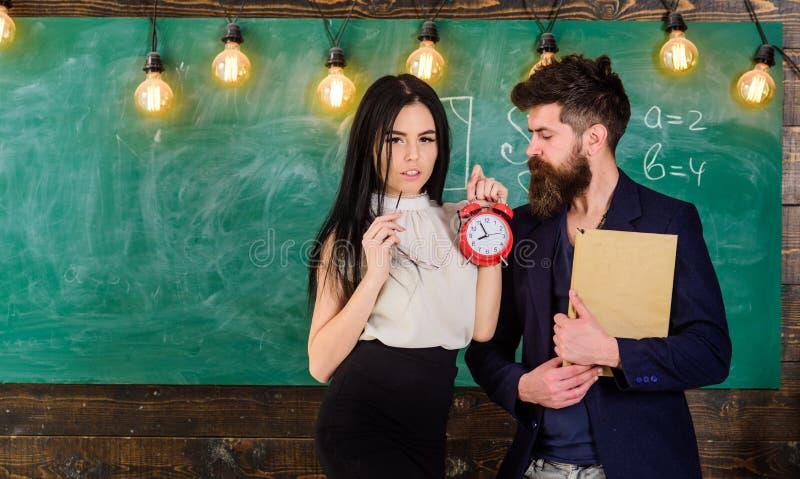 El profesor de la señora y el profesor estricto cuidan sobre disciplina y reglas en escuela Hombre con el libro del control de la fotos de archivo libres de regalías