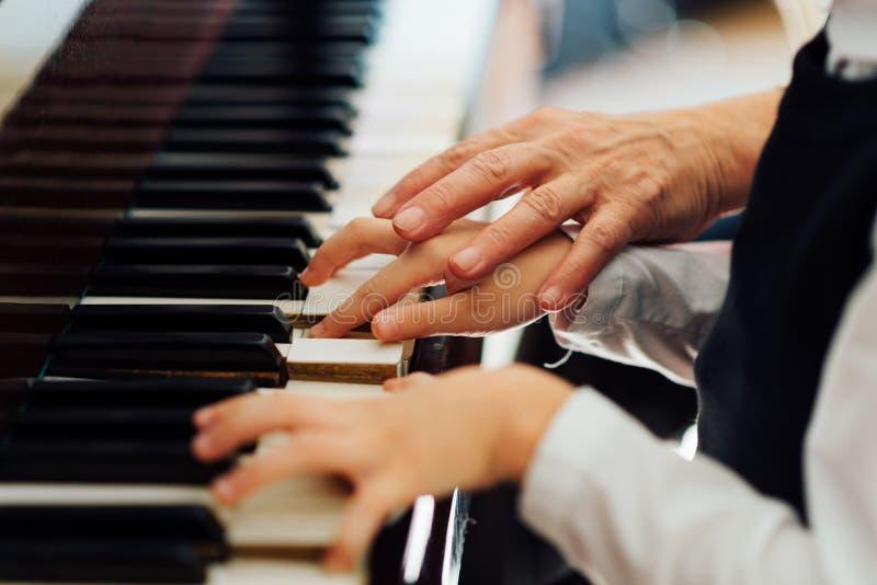 El profesor de música ayuda al estudiante a jugar correctamente imagen de archivo