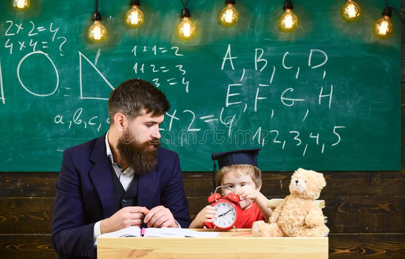 El profesor de sexo masculino joven dirige a su estudiante del niño al aprendizaje mientras que se sienta en sala de clase con ga fotos de archivo libres de regalías