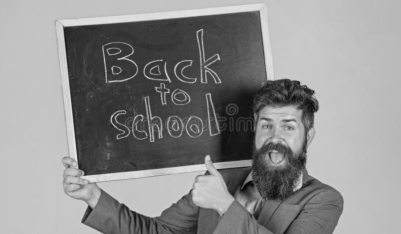 El profesor hace publicidad de nuevo a estudiar, comienza año escolar Invite para celebrar el día de conocimiento Soportes barbud foto de archivo