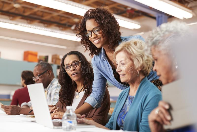 El profesor Helping Group Of retiró a las mujeres mayores que asistían a la clase de las TIC en centro de comunidad fotos de archivo libres de regalías