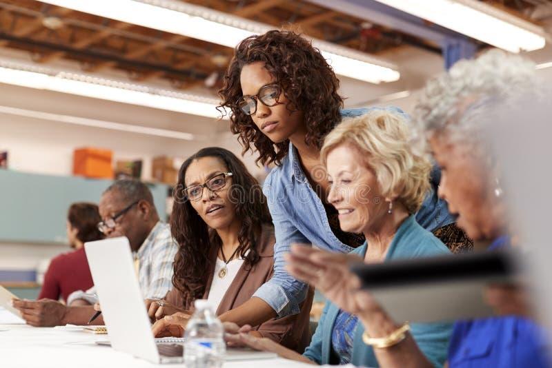El profesor Helping Group Of retiró a las mujeres mayores que asistían a la clase de las TIC en centro de comunidad imagenes de archivo