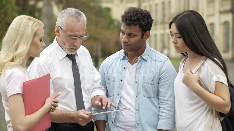 El profesor mayor que muestra el nuevo app educativo en la tableta a los estudiantes, MBI estudia fotos de archivo libres de regalías