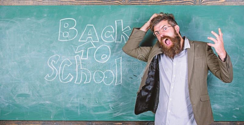 El profesor o el educador coloca la pizarra cercana con la inscripci?n de nuevo a escuela Grito infeliz del profesor hist?rico ca fotos de archivo libres de regalías