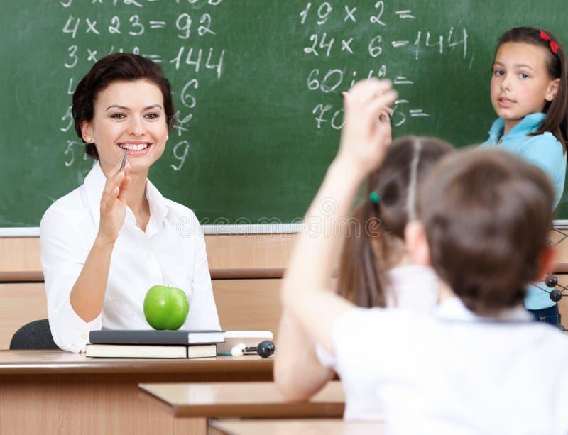 El profesor pregunta a pupilas en la álgebra imagen de archivo