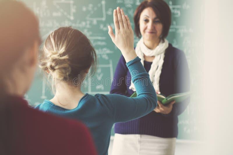 El profesor que hace la pregunta y la mano del estudiante se levantan la petición de contestar fotografía de archivo