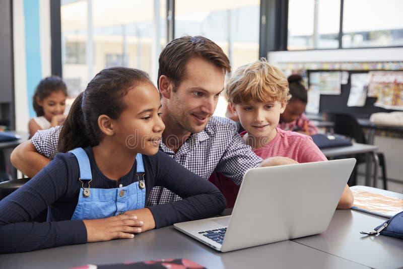 El profesor y dos estudiantes jovenes utilizan el ordenador portátil en clase foto de archivo libre de regalías
