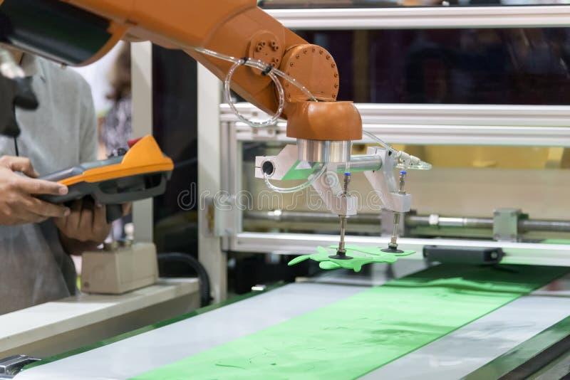 El programa experto del operador el brazo robótico para la cadena de producción foto de archivo