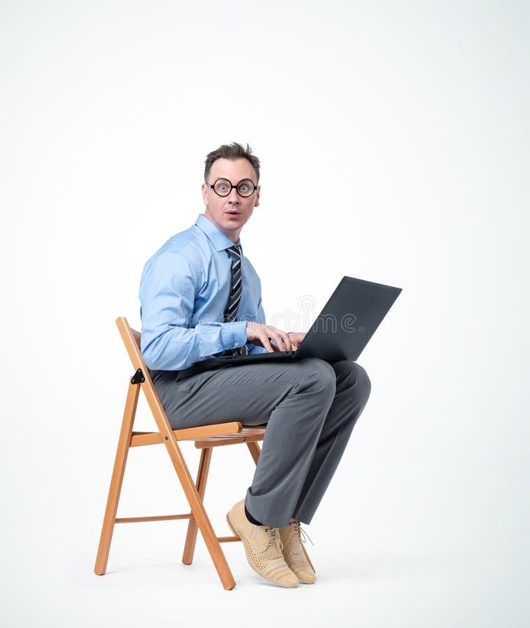 El programador de sexo masculino divertido en vidrios se está sentando en una silla con un ordenador portátil, en fondo imágenes de archivo libres de regalías