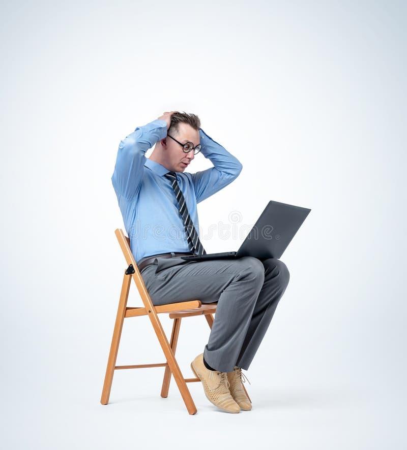 El programador de sexo masculino divertido se está sentando en una silla con un ordenador portátil que agarra su cabeza, en fondo fotografía de archivo libre de regalías